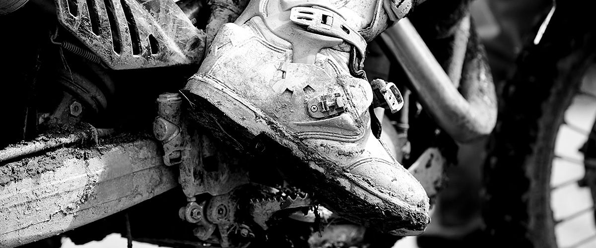 Muddy shoe on motorcycle close up