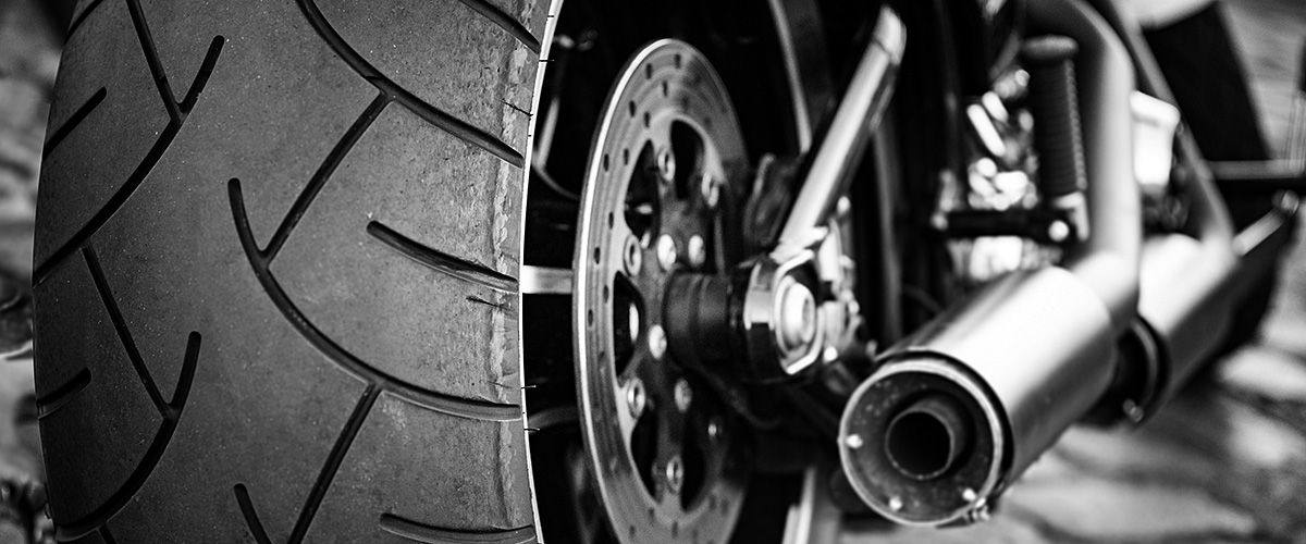 Black and white closeup photo of a motorcycle tire and exhaust